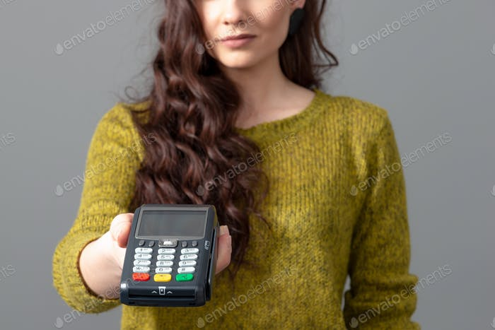 Frau mit drahtlosem, modernem Bankzahlungsterminal, um Kreditkartenzahlungen zu bearbeiten