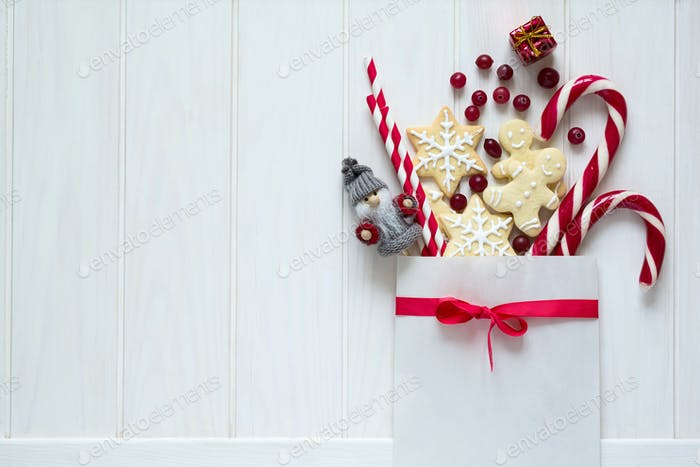 Christmas bag with gingerbread cookies and other sweets on white wooden background