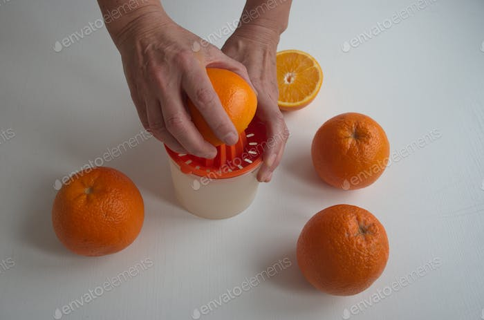 Cropped image of hands squeezing the orange