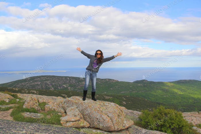 Woman standing on top of the world at Cadillac Mountain in Acadia National Park. Bar Harbor. Maine.