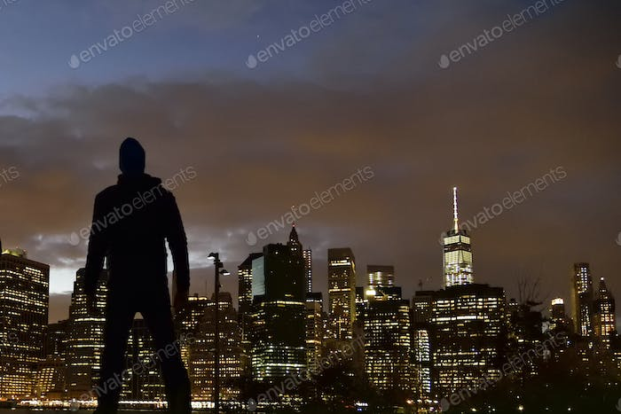 Silhouetted criminal against a Manhattan skyline at night