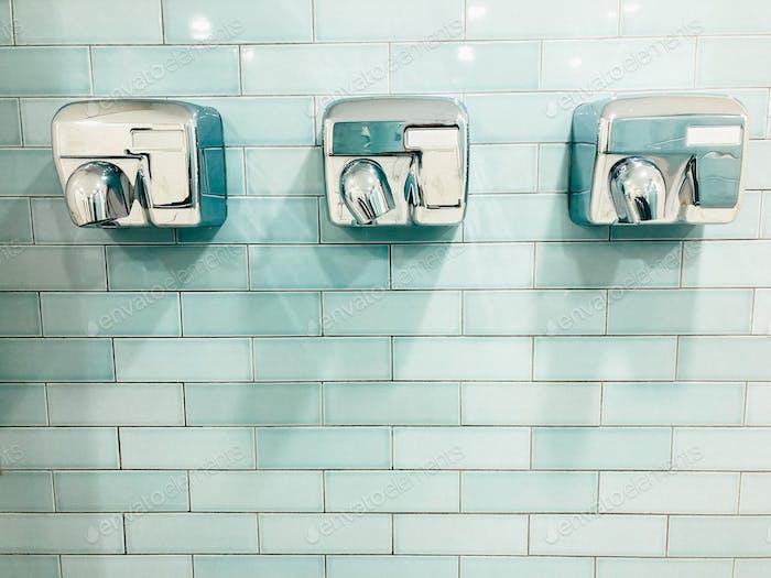 Secadoras de manos alineadas sobre el fondo de azulejos azul