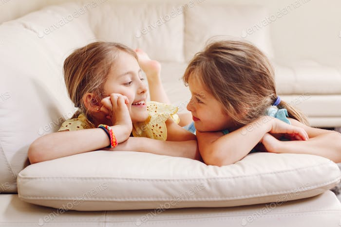 sisters; together; authentic; smiling; happy; girls; siblings; bonding; lying; couch; rest; relax; c