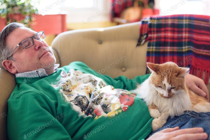 Awkward family photo 😂 Man in cat sweater napping after a big holiday meal