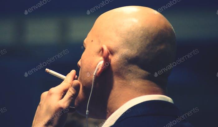 A bald man smoking