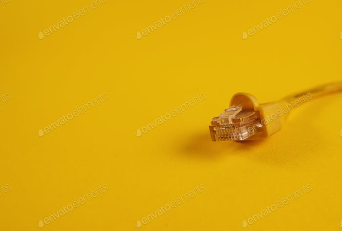 Yellow ethernet cable on yellow background. RJ45 jack, utp, network, internet.