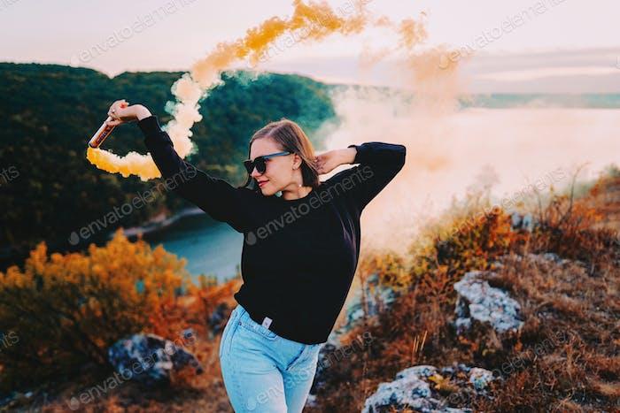 Schöne Frau tanzen mit Rauchbombe