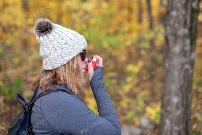 Woman using inhaler while hiking outdoors