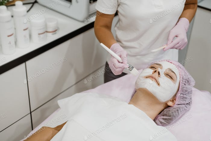 Cosmetologist applying mask on client's face in spa salon. Young woman getting facial care