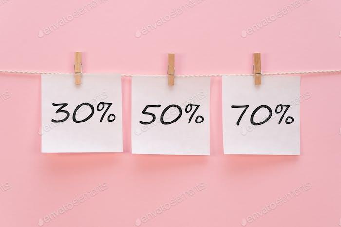 pegatina con el ícono 30% 50% 70%%% cuelga con una pinza de ropa en una cuerda sobre un fondo rosa