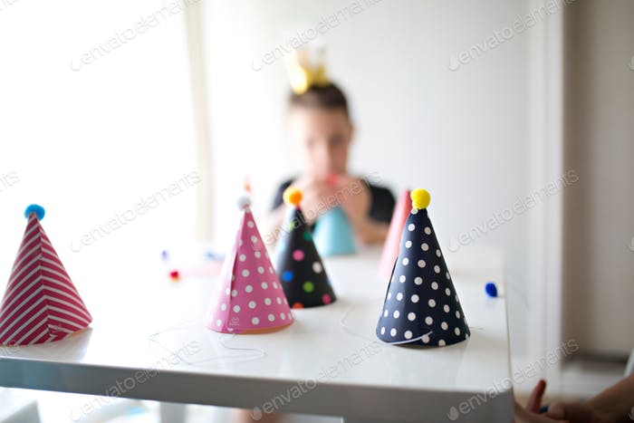 birthday party hats being made by kids on a table at home