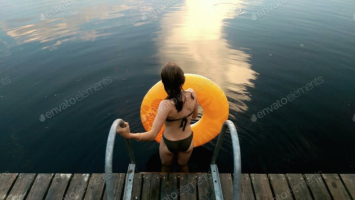 Lonely girl with water wheel ready for swimming on the lake at evening