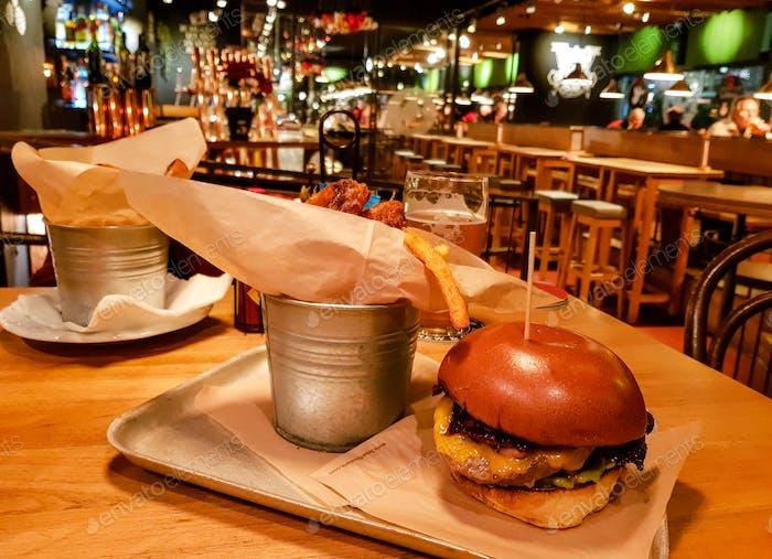 Бургер и картофель фри подаются на столе в пабе. Бургер на поддоне в закусочной.