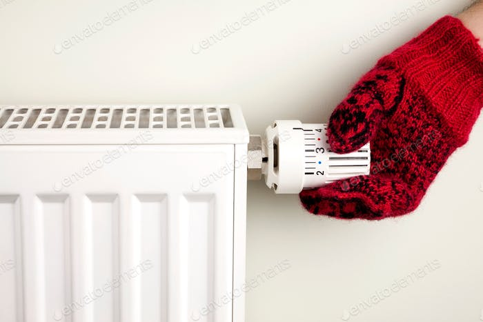 Single human hand with knitted glove turning radiator thermostat, winter concept