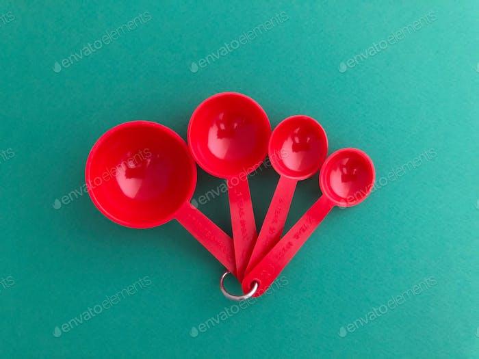 Leuchtend rote Esslöffel und Teelöffel auf grünem Hintergrund