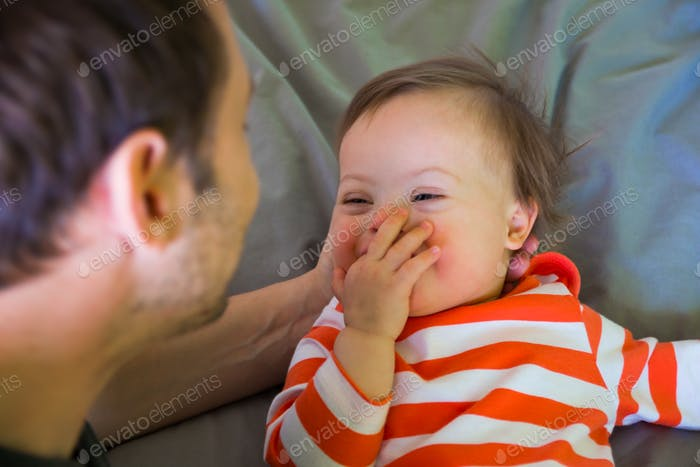 Cute baby boy with Down syndrome playing with father