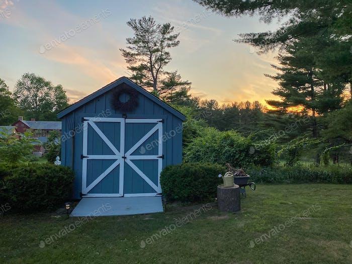 Голубой садовый сарай на пригородном заднем дворе.