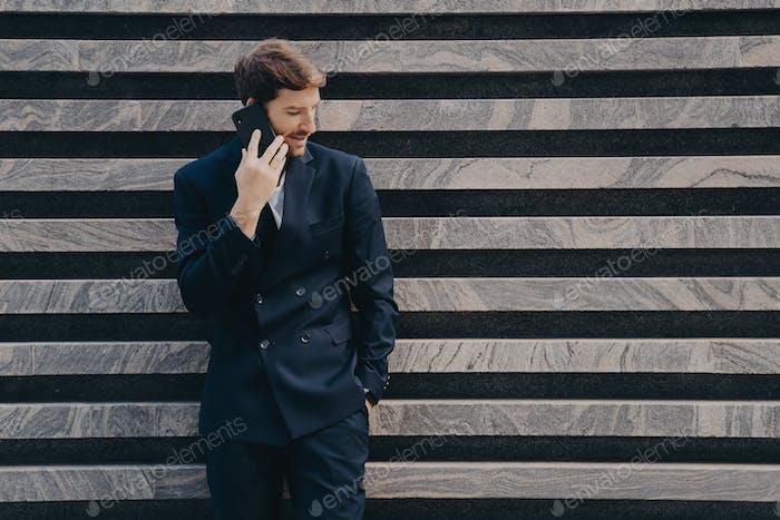 Businessman in elegant black clothes phones to partner focused down keeps smartphone