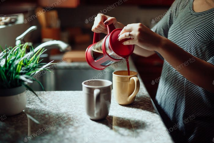 Girl pours coffee from a french press into a coffee cup.