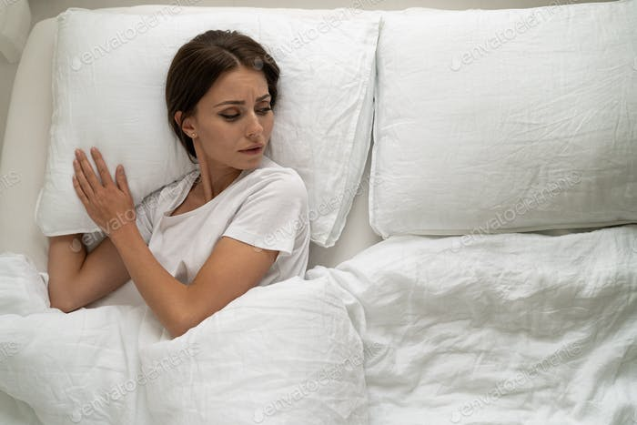 Top view of sad woman lying in bed alone, looking to aside, feeling lonely after quarrel or divorce