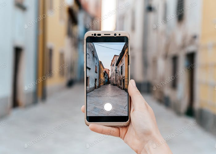 Personal perspective of hand holding mobile phone, taking photos, Town, travel, picture in picture.