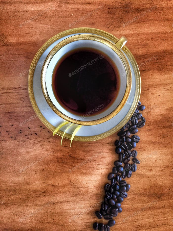 Black rich coffee with lemon zest from above.