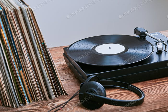 Stack of black vinyl records, turntable vinyl player and headphones. Classic stereo set. Music hobby