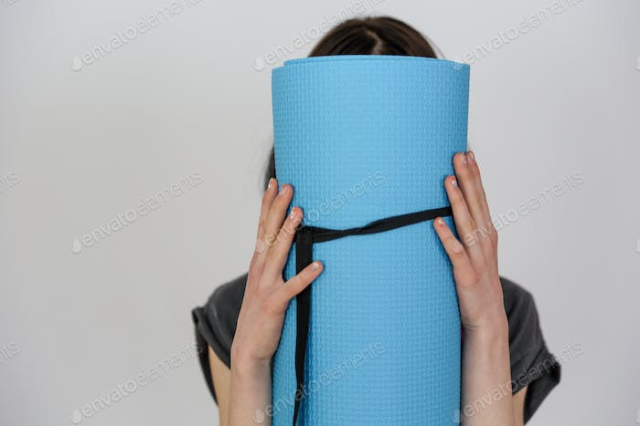 Girl with yoga mat on a white background