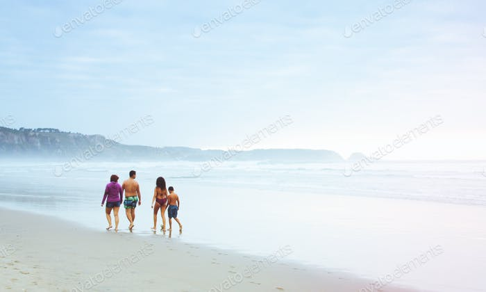 Rear view of four people walking on the beach in a cloudy day of summer. Asturias, Castrillón, Salin