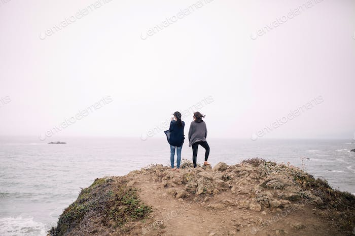 Girls standing on cliffs at Sonoma Coast