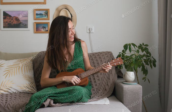 A young woman playing on ukulele sitting on the couch at home, hobby, music, musician, guitar, apart