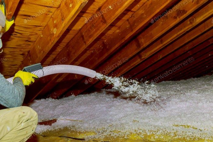 Technician spraying blown Fiberglass Insulation between Attic Trusses foam insulation repair tool in