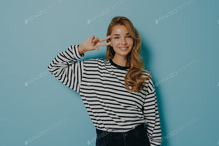 Portrait of attractive charming smiling woman in casual clothes gesturing v-sign isolated on blue
