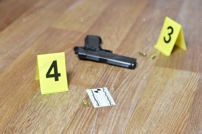 Crime scene investigation concept - Pistol and bullet shell against the yellow crime marker on