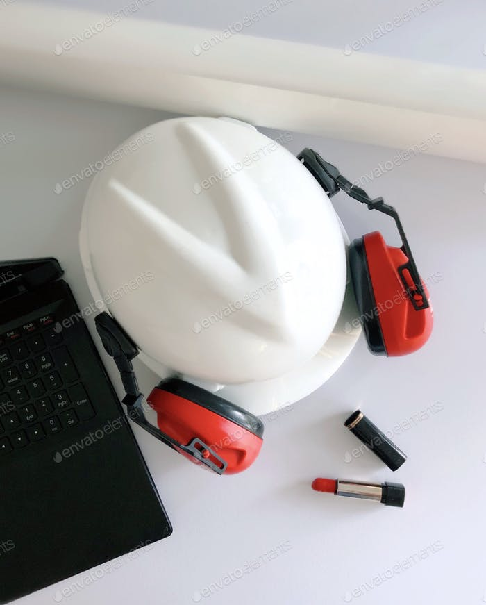 Flat lay of an engineer woman's  essentials. Her safety hard hat, laptop, building plans & lipstick