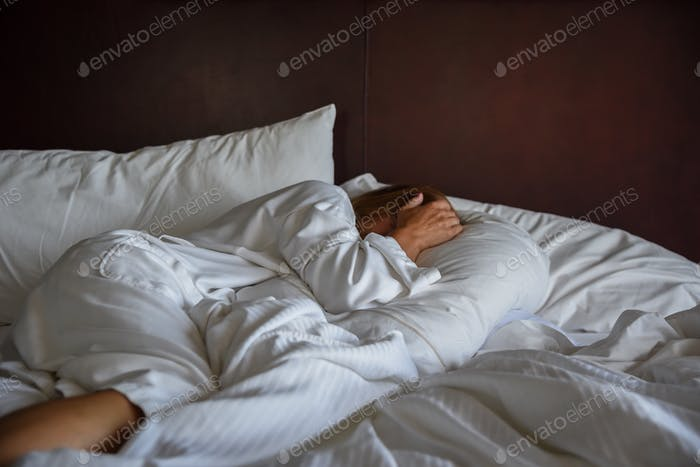 Woman laying in bed covering head