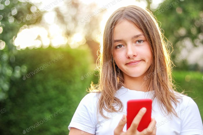 Close-up portrait of teenager girl with sceptical facial expression holding smartphone in hand