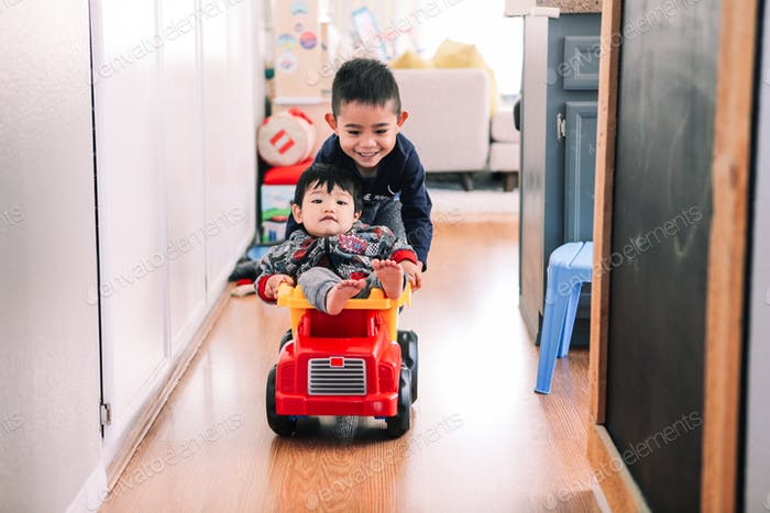 Older brother pushing his younger brother through a hallway at home while riding in a toy dump truck