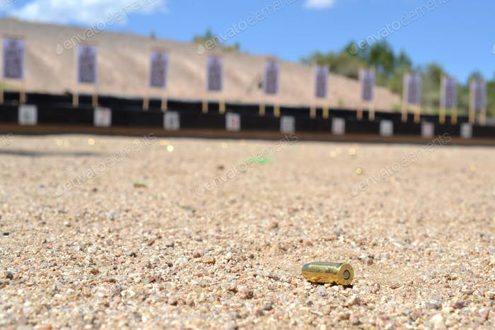 Ammunition casing spent shell laying on the ground with the shooting range targets in the background