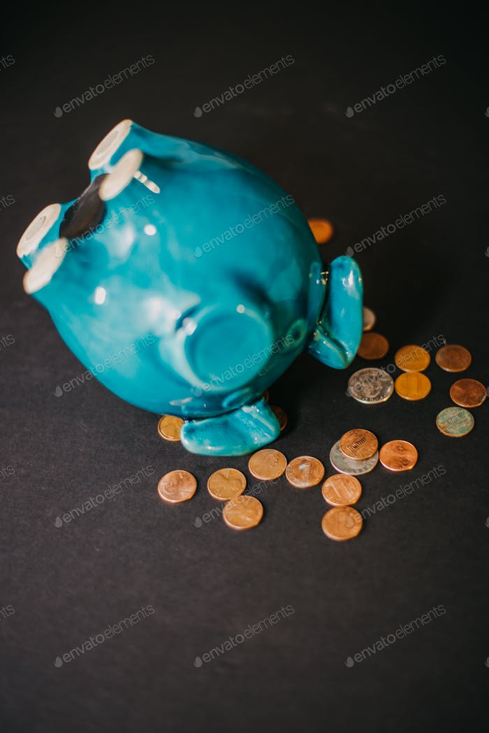 A piggy bank upside down with coins falling out