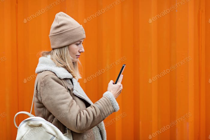 Beautiful young caucasian woman 20-30 years old in casual clothing using smartphone on orange