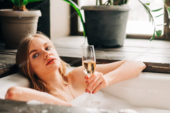 Beautiful young blonde woman in the bathroom with bubbles drinking a glass of white wine