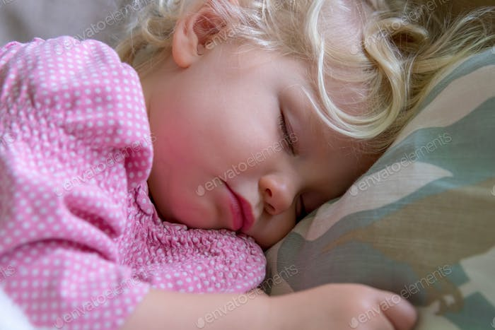 Sleeping toddler girl with blonde curly hair