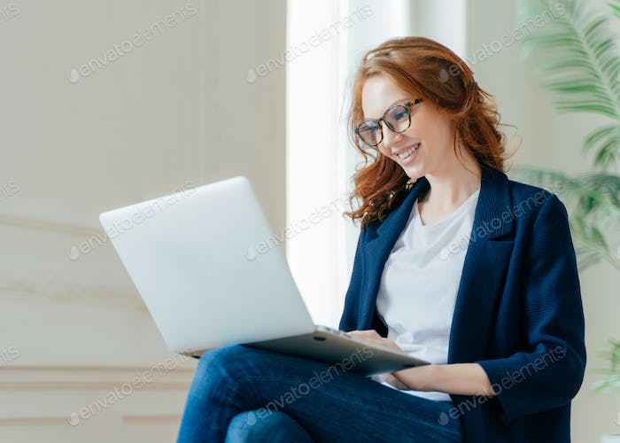 Professional female employer enjoys working process, sits crossed legs with laptop.