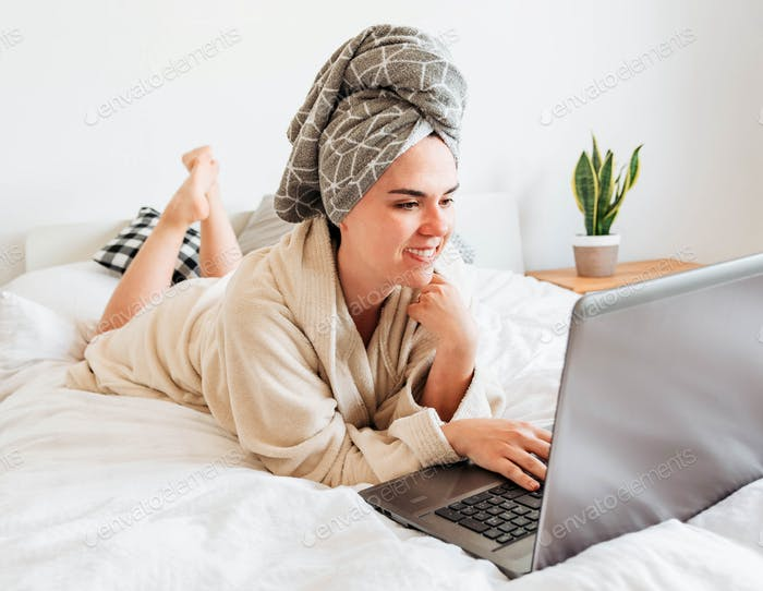 Young woman on bed, video chatting with friends. Video call, laptop, using laptop, computer, quarant