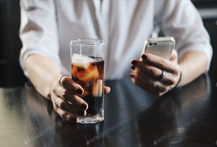 Das Mädchen schreibt die Nachricht auf das iPhone und trinkt Coca-Cola