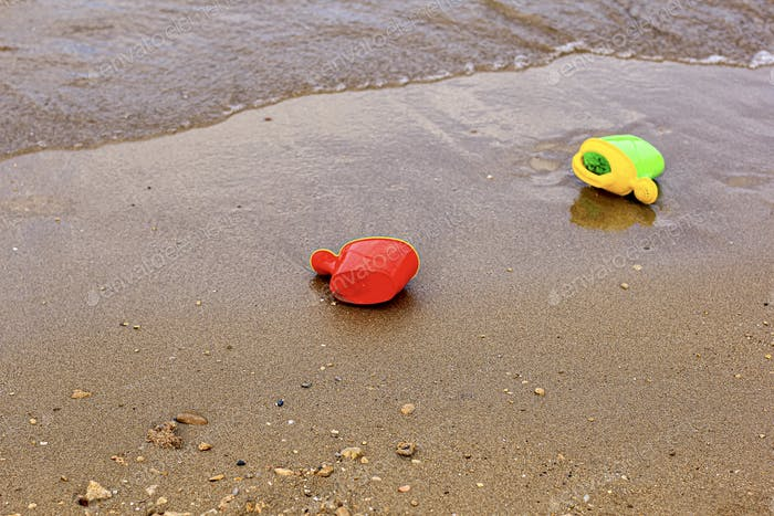 Forgotten children's plastic toys on the beach. Concept of vacation, travel, summertime, holidays.