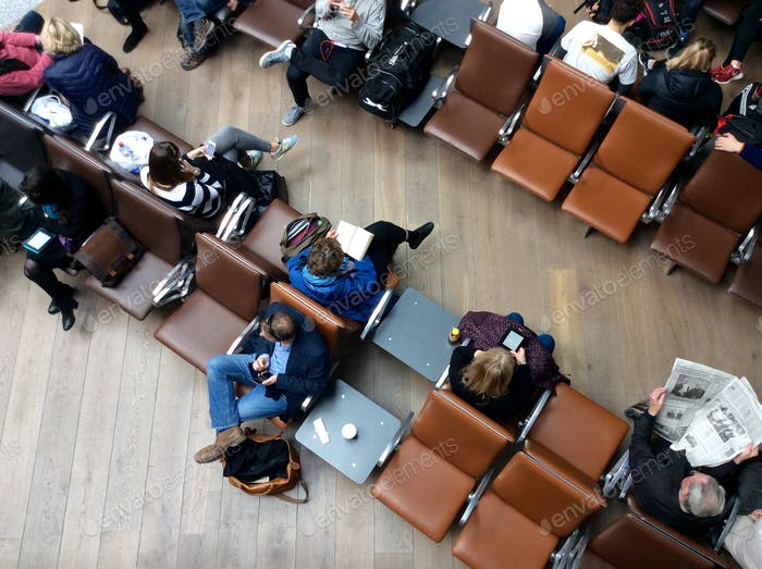 Rows of people waiting In airport chairs