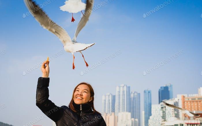 Girl playing with birds at Haeundae beach, Busan, South Korea