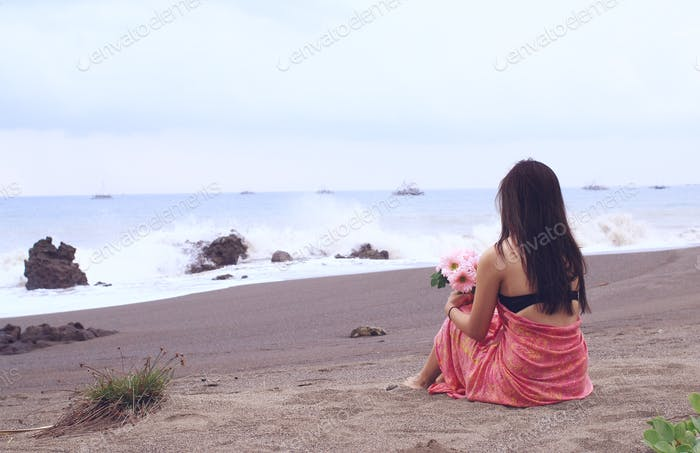 A girl sitting on the beach.